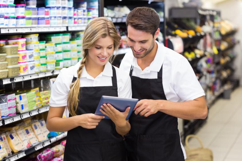 Dois colegas de trabalho utilizando um tablet digital para planejar a expansão de supermercados