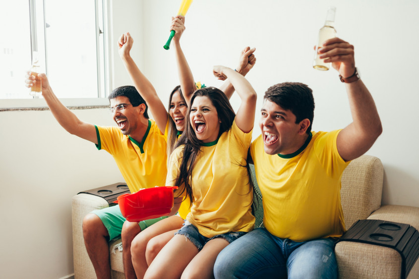Group of friends watching soccer game on television, celebrating goal and screaming